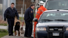 Members of the RCMP investigate the scene of an apparent shooting and house fire located near a school in Surrey, B.C., Friday, March 25, 2011. (THE CANADIAN PRESS/Jonathan Hayward)