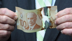 Finance Minister Jim Flaherty holds a new polymer-based $100 bill as he takes part in the unveiling of the new polymer bank notes in $50 and $100 denominations at the Bank of Canada in Ottawa on Monday, June 20, 2011. (Sean Kilpatrick / THE CANADIAN PRESS)
