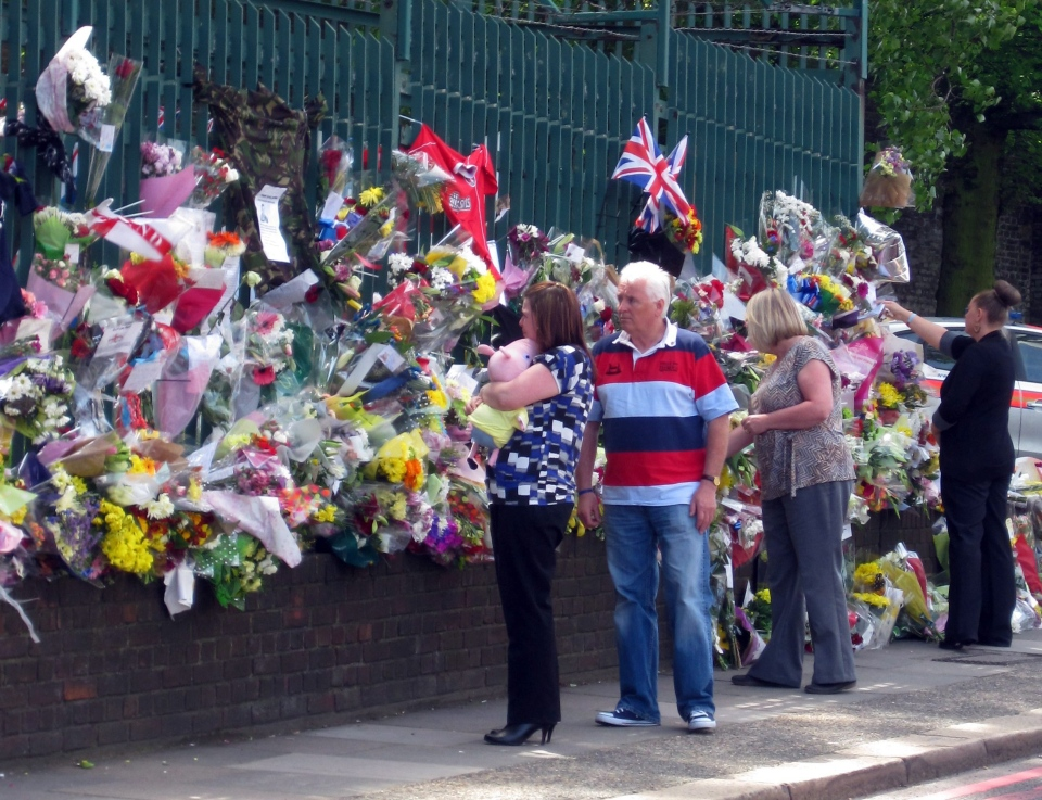 Drummer Lee Rigby's widow Rebecca Rigby, clutching a soft toy, joins other unidentified family members as they look at floral tributes left by well wishers outside Woolwich Barracks as they visited the scene of the 25-year-old soldier's murder in Woolwich, south-east London, Sunday, May 26, 2013. (AP / Jennifer Cockerill)