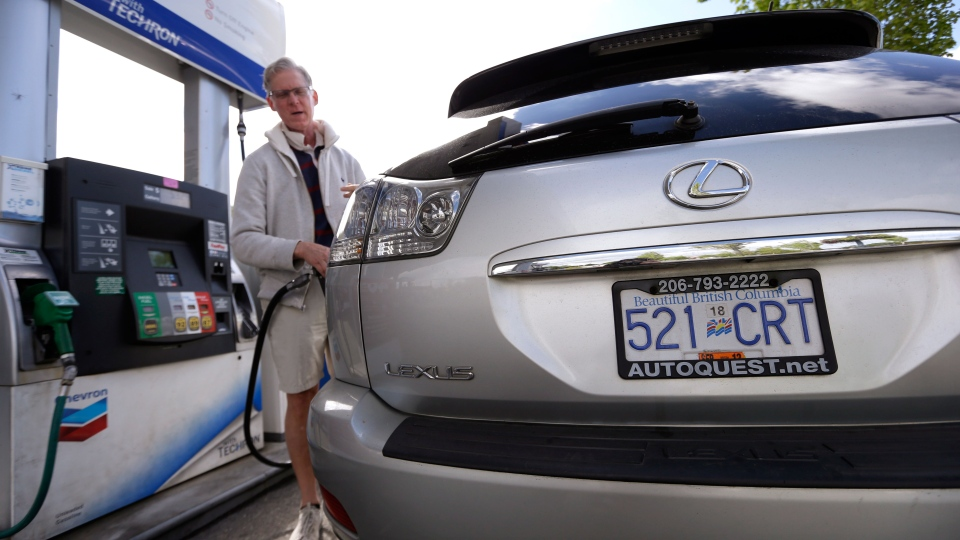 Curt Griffiths, from nearby White Rock, B.C., pumps gas at a station in Blaine, Wash., Thursday, May 23, 2013. (AP / Elaine Thompson)
