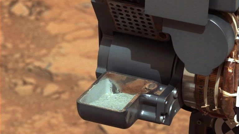 The Curiosity rover holds a scoop of powdered rock on Mars. (NASA)