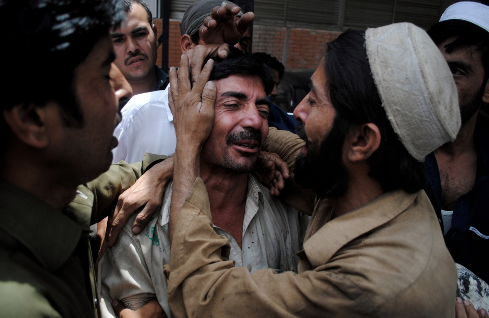 People comfort a family member of a female polio worker who was killed by unknown gunmen, at a local hospital in Peshawar, Pakistan, Tuesday, May 28, 2013. (AP / Mohammad Sajjad)