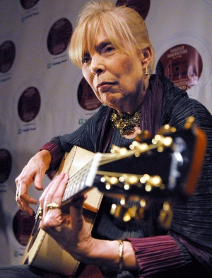 Joni Mitchell, right, plays a guitar presented to her by guitar makers Robin and Claude Boucher (not shown) at the Canadian Songwriters Hall of Fame Gala in Toronto, Sunday, January 28, 2007. (Aaron Harris / THE CANADIAN PRESS)