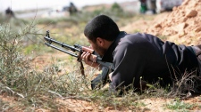 A Libyan rebel returns fire after being ambushed by forces loyal to Muammar Gaddafi some 120 km (75 miles) east of Sirte in eastern Libya, Monday, March 28, 2011. (AP Photo)