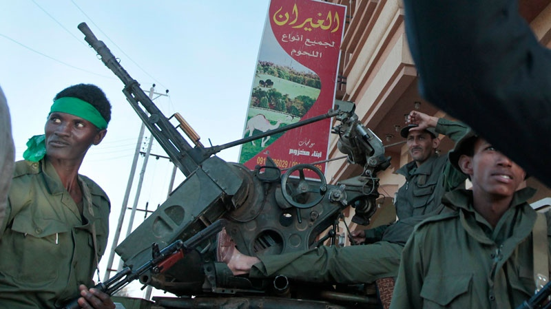 In this image taken during an organized trip by the Libyan authorities, armed Libyan soldiers loyal to Moammar Gadhafi are seen on a street under their control in Mistrata, 200 kms (120 miles) east of Tripoli, Libya, Monday March 28, 2011. (AP / Jerome Delay)