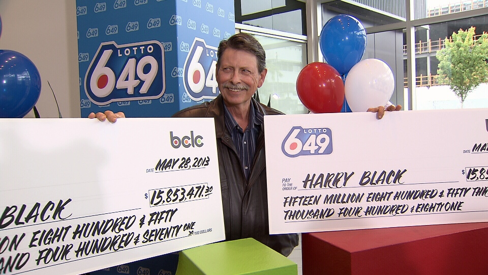 Harry Black collects his two cheques for $31.7 million from the record high 6/49 jackpot. (CTV)