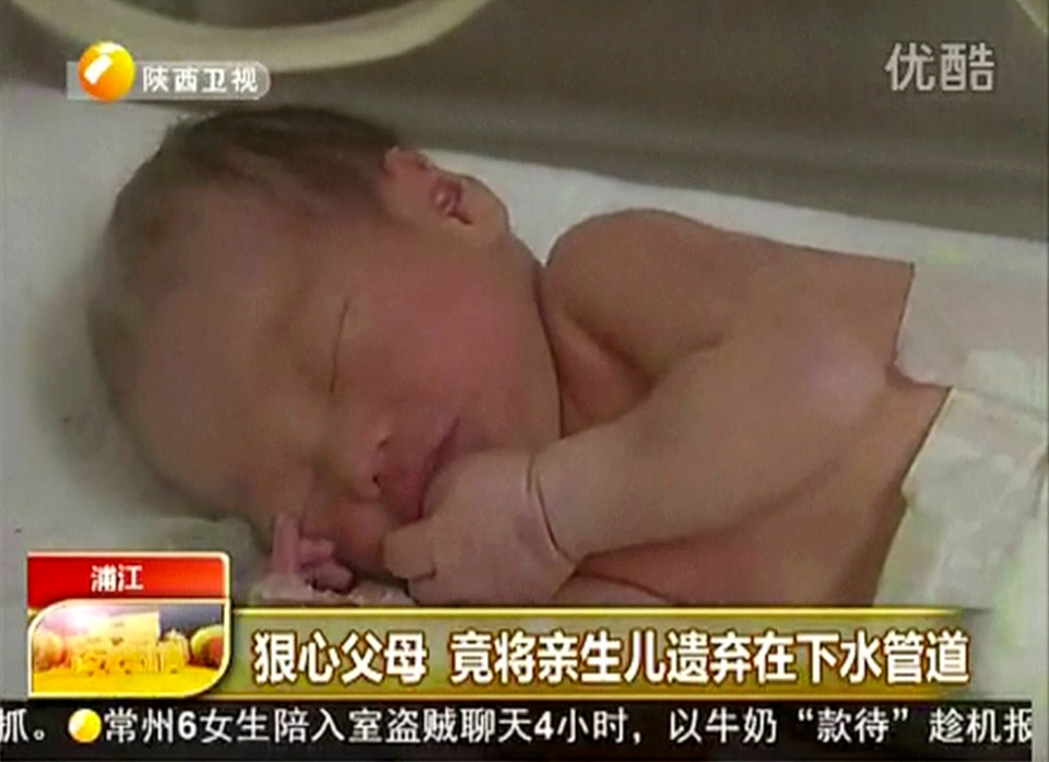 A baby who was rescued after being trapped in a sewage pipe just below a squat toilet in a public building, lies on a bed at a hospital in Jinhua city, eastern China, May 25, 2013. (Shaanxi TV)
