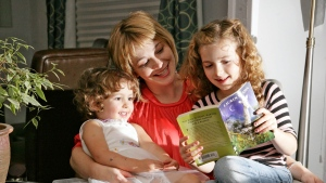 Angela Sasseville and her two daughters Cosette, 2, left, and Oriel, 7, read a book at their Denver home in this 2008 file photo. (AP Photo/Jack Dempsey)