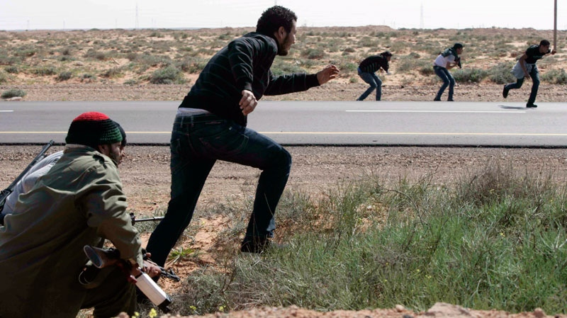 Libyan rebels take cover after being ambushed by forces loyal to Moammar Gadhafi some 120 km (75 miles) east of Sirte in eastern Libya, March 28, 2011. (AP Photo)