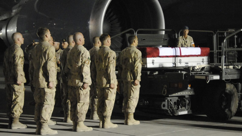 Comrades of Canadian Cpl. Yannick Scherrer bid farewell to the slain soldier during an overnight ramp ceremony at Kandahar Airfield, Tuesday, March 29, 2011. (Tara Brautigam / THE CANADIAN PRESS)