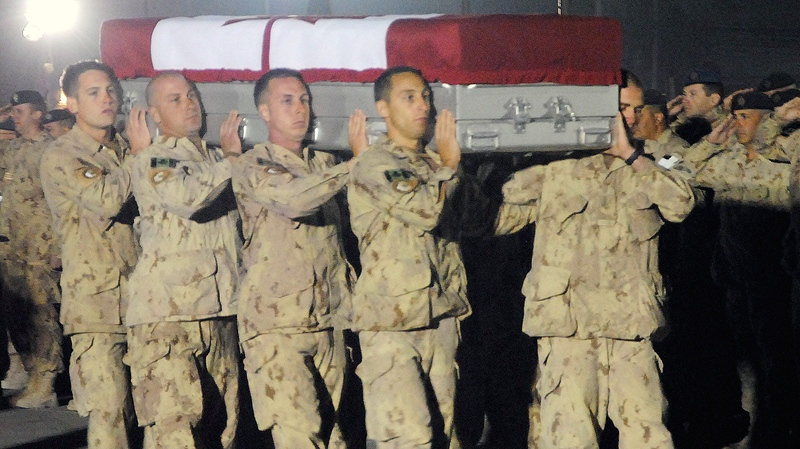 Comrades of Canadian Cpl. Yannick Scherrer carry his flag-draped casket during an overnight ramp ceremony at Kandahar Airfield, Tuesday, March 29, 2011. (Tara Brautigam / THE CANADIAN PRESS)