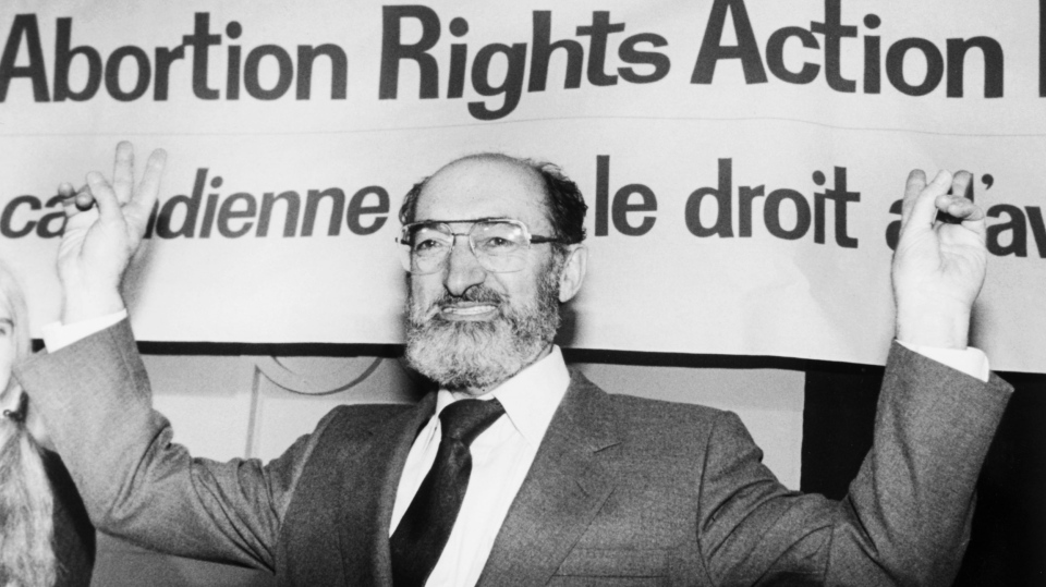 Dr. Henry Morgentaler raises his arms in victory at a news conference in Toronto, Ont., Jan. 28, 1988. (Blaise Edwards / THE CANADIAN PRESS)