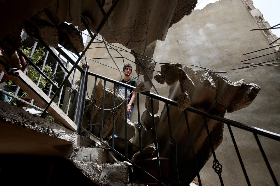 Mohammad Awad, 16, is seen through destruction after a rocket fired by Syrian rebels hit Hermel town in northeast Lebanon on May 29, 2013. (AP / Hussein Malla)