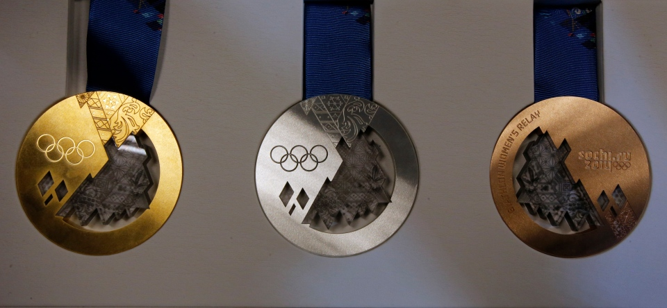 Gold, silver and bronze medals are displayed for journalists during a presentation of Sochi 2014 Olympic medals in St. Petersburg, Russia on May 30, 2013. (AP Photo/Dmitry Lovetsky)
