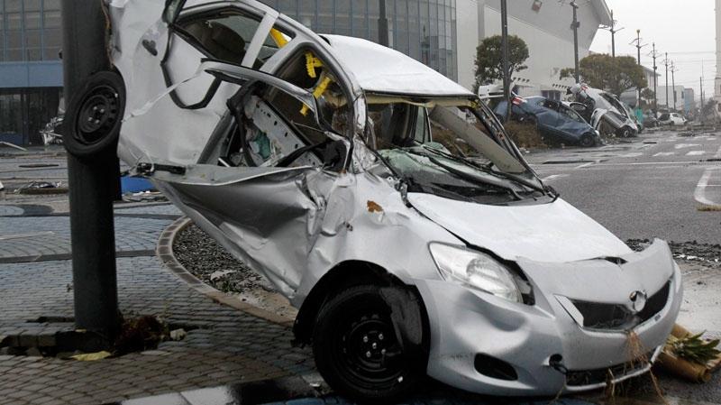A Toyota Yaris compact sedans lie damaged at Sendai port, Miyagi Prefecture, Japan on March 15, 2011. (AP / Koji Sasahara)