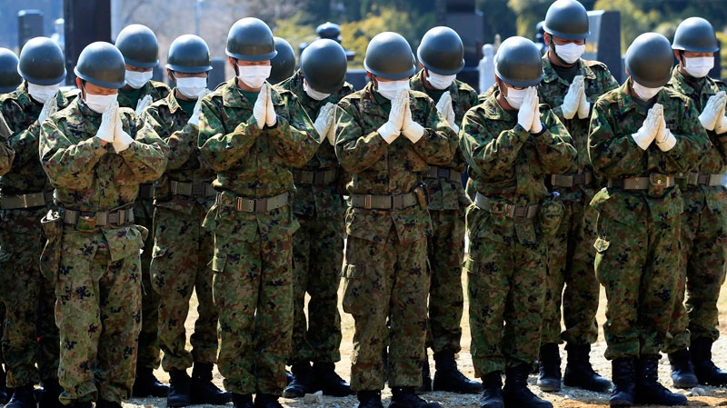 Members of the Japan Ground Self-Defense Force pray for victims of the March 11 earthquake and tsunami at a mass grave site in Yamamoto, Miyagi Prefecture, northeastern Japan, Tuesday, March 29, 2011.  (AP / Eugene Hoshiko)