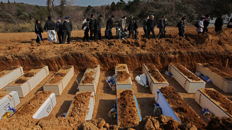 Relatives walk past coffins containing victims of the earthquake and tsunami during a mass funeral in Yamamoto, northeastern Japan, Tuesday, March 29, 2011.(AP / Vincent Yu)