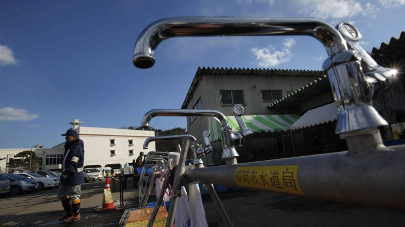 A worker from a water supply department walks by water faucets set up for survivors at a shelter in the devastated town of Yamamoto, Miyagi Prefecture, northeastern Japan, Monday, March 28, 2011. The March 11 quake off Japan's northeast coast triggered a tsunami that barreled onshore and disabled the Fukushima nuclear complex. (AP Photo/Vincent Yu)