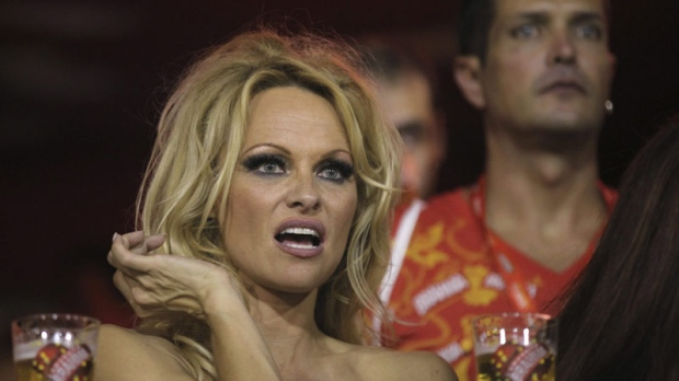 Pamela Anderson gestures from the stands as she watches a carnival parade at the Sambadrome in Rio de Janeiro, Brazil, Sunday March 6, 2011. (AP Photo/Silvia Izquierdo)