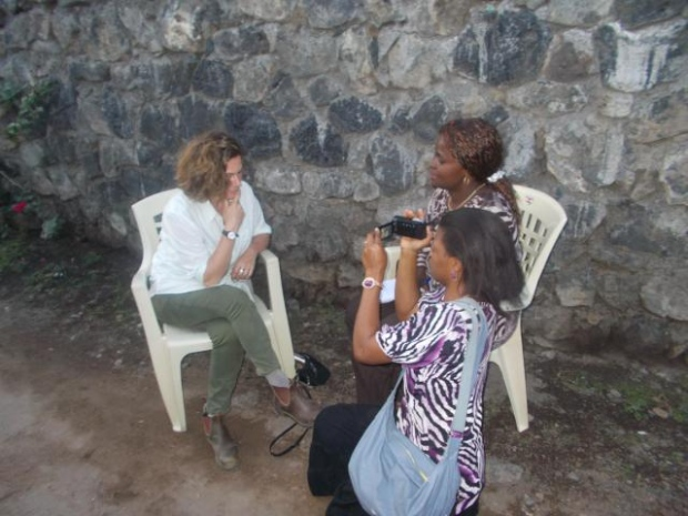 An interview with Helene for her weekly broadcast on women's issues in Goma. Fifi does the camera work in this lava-encrusted lane, doubling as a studio.