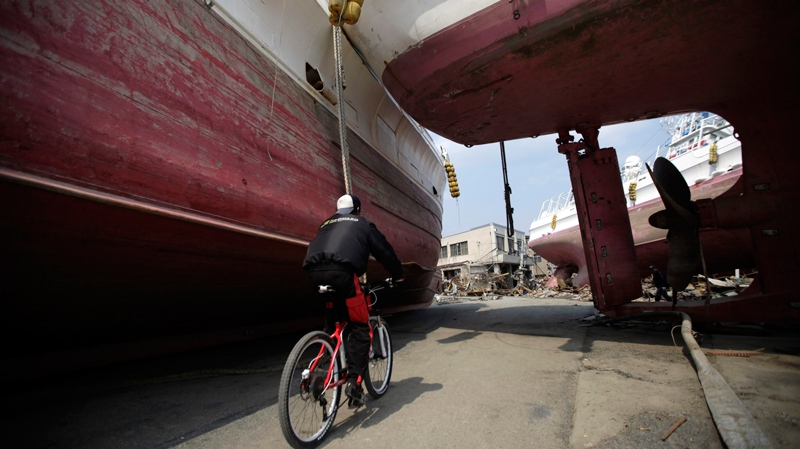 A man rides a bicycle in between the ships that were washed ashore in Kesennuma, Miyagi Prefecture, northern Japan, Wednesday, March 30, 2011. (AP / Eugene Hoshiko)