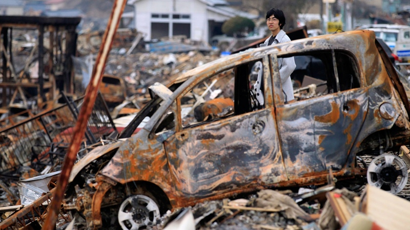 A man looks at the town which was burned to the ground by the earthquake and tsunami Wednesday, March 30, 2011 in Kesennuma, Miyagi Prefecture, northern Japan. (AP / Eugene Hoshiko)