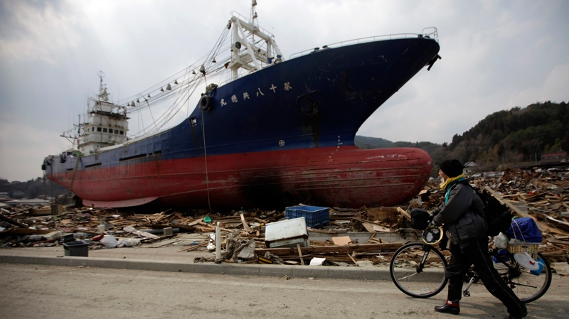 A man with his bicycle walks near a ship that was washed ashore in Kesennuma, Miyagi Prefecture, northern Japan, Wednesday, March 30, 2011. (AP / Eugene Hoshiko)