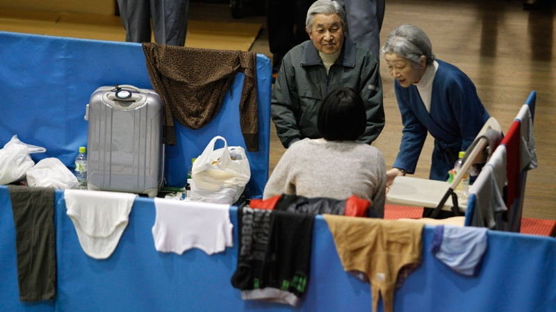 Japan's Emperor Akihito, left, and Empress Michiko talk with an evacuee at an evacuation center in Tokyo Wednesday, March 30, 2011. Emperor and Empress visited the shelter to encourage some 300 evacuees, mostly from Fukushima Prefecture where the troubled Fukushima Dai-ichi nuclear power plant is located. (AP / Issei Kato)