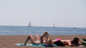 In this file photo, people read as they sunbathe on a warm summer day at Cherry Beach in Toronto on Thursday, Aug. 23, 2012. (The Canadian Press/Michelle Siu)