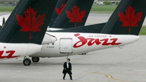 A pilot inspects his plane at the terminal for Air Canada's discount airline Jazz at Dorval airport in Montreal Friday, May 30, 2003.