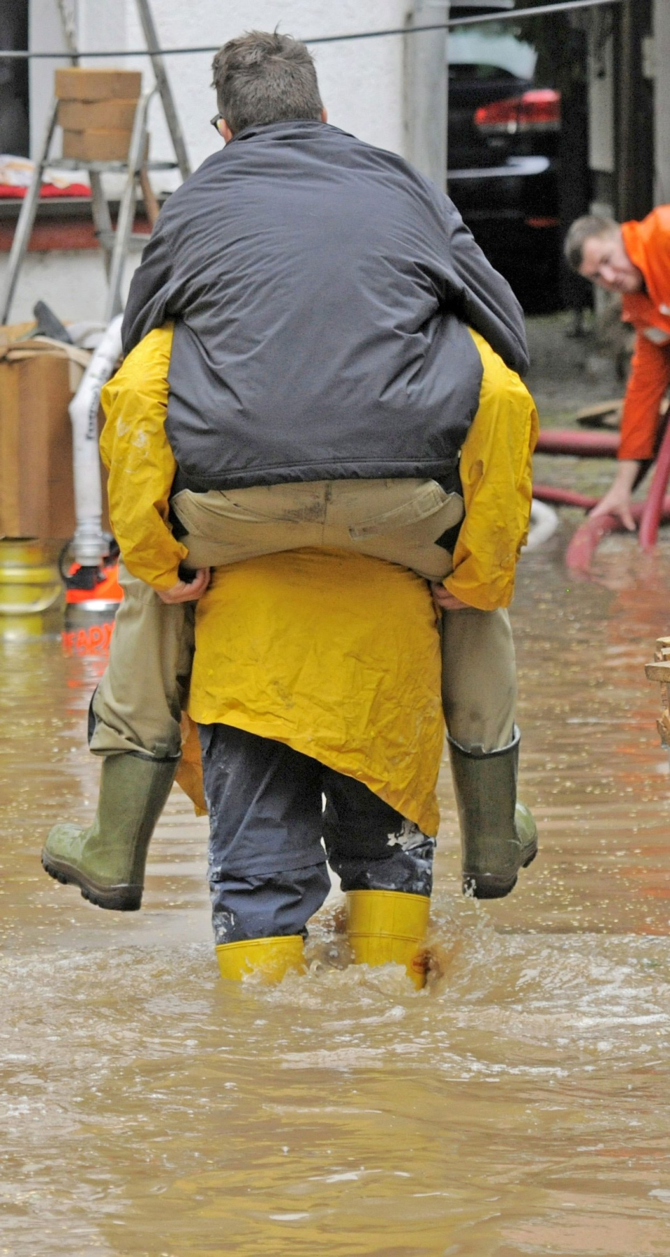 A helper carries a man along a flooded area by river the river Roda in Hainbuecht near Stadtroda, central Germany, Friday, May 31, 2013. (AP / Jens Meyer)