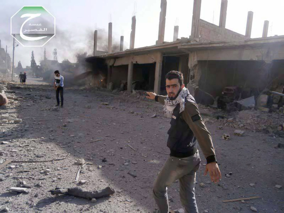 Qusair-based activist Hadi Abdullah, right, walks on a street hit by the shelling of Hezbolllah Lebanese Shiite group and the Syrian forces loyal to Syrian President Bashar Assad, in the town of Qusair, near the Lebanon border, Homs province, Syria, Friday, May 31, 2013. (Qusair Lens)