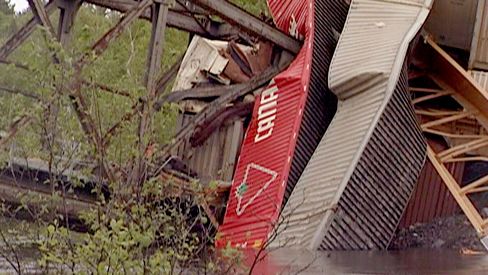 A collapsed bridge cuts in to a train car over the Wahnapitae River near Sudbury, Ont., in this image taken from video on Sunday, June 2, 2013. (CTV Northern Ontario)