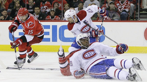 Carolina Hurricanes' Tuomo Ruutu (15), of Finland, controls the puck as Montreal Canadiens' Brian Gionta (21) chases and P.K. Subban falls to the ice during the second period of an NHL hockey game in Raleigh, N.C., Wednesday, March 30, 2011. (AP Photo/Gerry Broome)