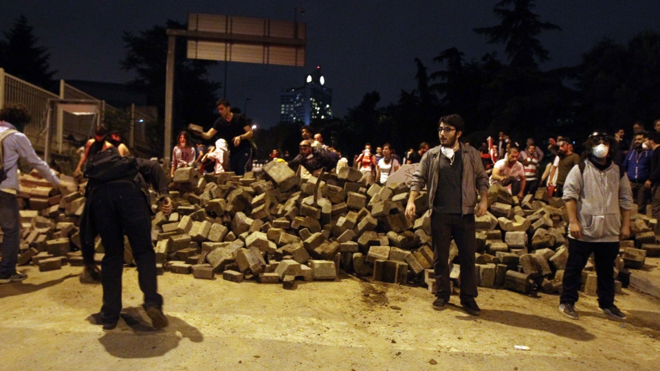 Protesters reinforce a barricade with stones during the third day of nationwide anti-government protest near the Prime Minister's office at Besiktas area in Istanbul, late Sunday, June 2, 2013. (AP / Thanassis Stavrakis)