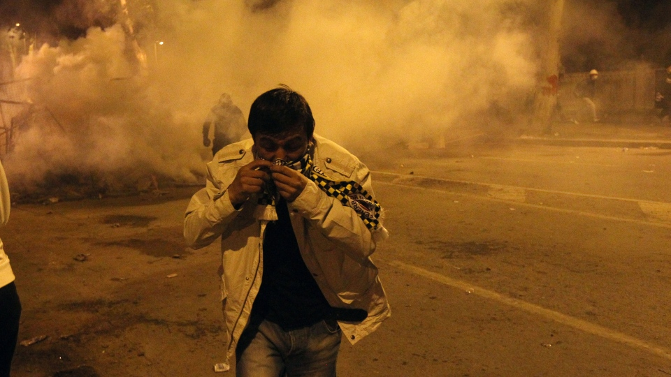 A protester runs to avoid tear gas during the third day of nationwide anti-government protest near the Prime Minister's office at Besiktas area in Istanbul, late Sunday, June 2, 2013. (AP / Thanassis Stavrakis)
