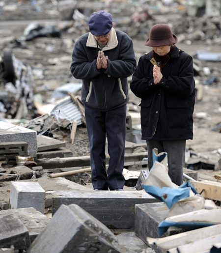 A couple offers prayers before the collapsed family grave stone at a cemetery following the March 11 tsunami triggered by a massive earthquake in Ishinomaki, Miyagi Prefecture, northeastern Japan, Thursday, March 31, 2011.(AP / Kyodo News)