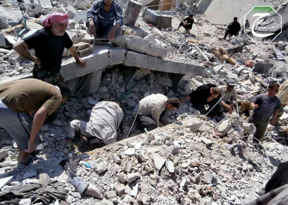 Syrian citizens inspect the rubble of buildings that were damaged from an air strike from Syrian forces in the town of Qusair, near the Lebanon border, Homs province, Syria, Tuesday, May 21, 2013. (Qusair Lens)