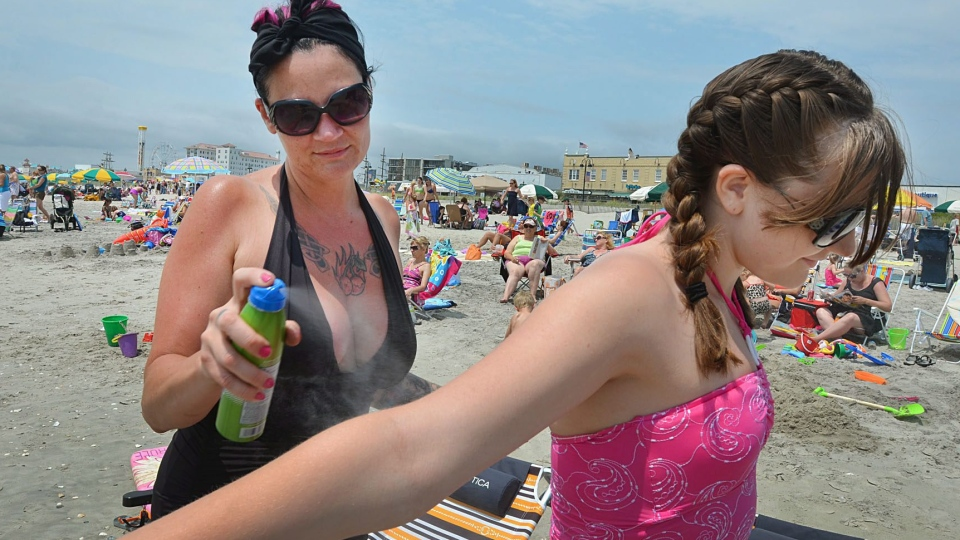 Suzanna Myers, of Chalfont Pa., applies sunscreen on her daughter, Kiley Plenderleith, 12, in Ocean City, N.J., on June 19, 2012. (The Press of Atlantic City / Ben Fogletto)