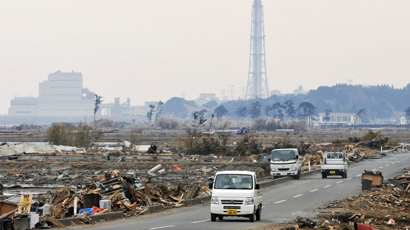 Small trucks drive through a road with a backdrop of Fukushima nuclear power plants, within near 30 kilometers' area from the crippled Fukushima Dai-Ichi power plant in Minamisoma, Fukushima Prefecture, northern Japan, Wednesday, March 30, 2011. (Kyodo News)