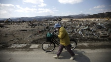 A woman pushes her bicycle at the March 11 earthquake and tsunami devastated area in Rikuzentakata, Iwate Prefecture, northern Japan Friday, April 1, 2011. (AP Photo/Eugene Hoshiko)
