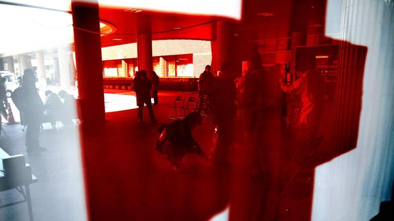 A reflection shows evacuees being screened for radiation contamination before entering an evacuation centre in Fukushima, Japan, Friday, April 1, 2011. (AP / Wally Santana)