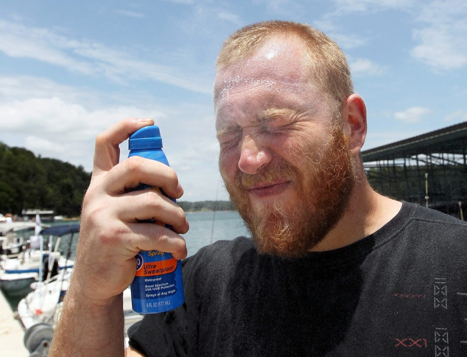 Atlanta Falcons offensive lineman Sam Baker sprays himself on the face with sunscreen before leaving the dock for Fishing With the Falcons near Buford, Ga on Lake Lanier, Tuesday, June 12, 2012. (Atlanta Journal and Constitution / Curtis Compton)