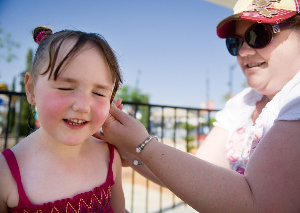 Peyton Hawkins, 5, gets her mother's loving touch of sunscreen before they play a game of miniature golf at Boomers in Irvine, Calif., on Sunday, May 12, 2013. (The Orange County Register / Mindy Schauer)