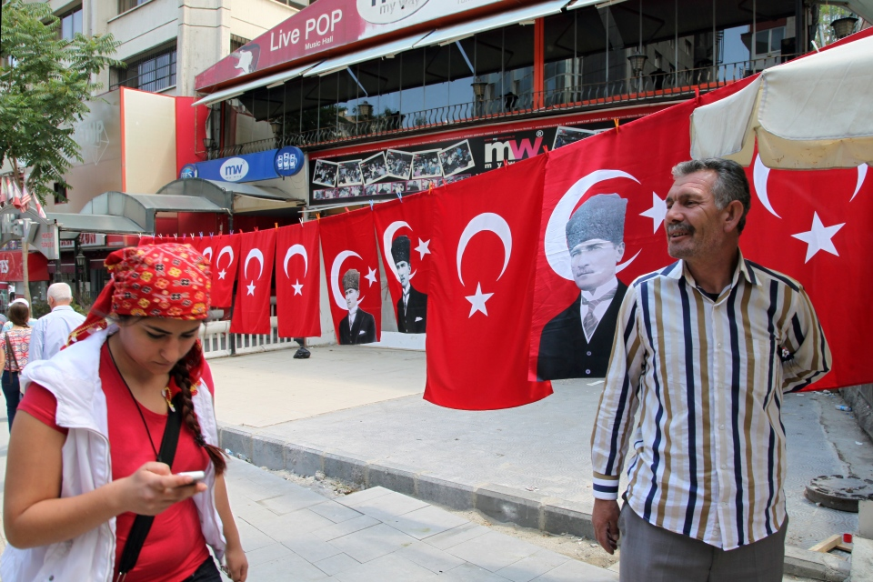 A street vendor seen with his national flags and posters of Turkey's founder Kemal Ataturk, in Kizilay Square in the main city centre of Ankara, Turkey, Wednesday, June 5, 2013. (AP Photo/Burhan Ozbilici)