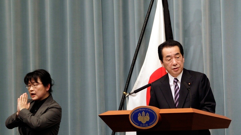 With a mourning ribbon hung on the Japanese flag, Japan's Prime Minister Naoto Kan, accompanied by a sign language interpreter, during a press conference in Tokyo Friday, April 1, 2011. (AP / Koji Sasahara)