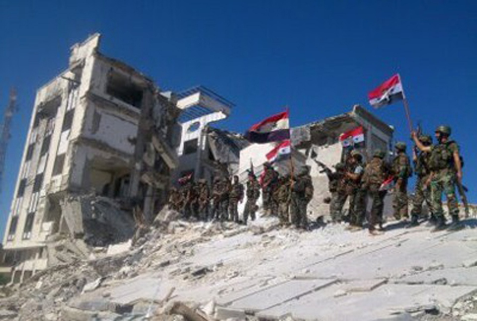 Syrian army troops hold up national flags in the town of Qusair, near the Lebanon border, Homs province, Syria, Wednesday, June 5, 2013. (SANA)