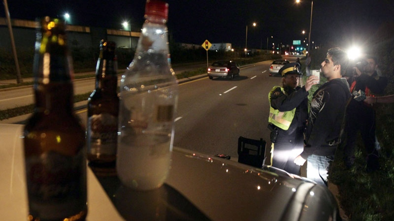 Open bottles of alcohol found in a motorist's car sit on the vehicle as RCMP Cnst. Kim True conducts a breathalyzer test on the driver during a roadside check in Surrey, B.C., just before midnight on Friday, Sept. 24, 2010. (Darryl Dyck / THE CANADIAN PRESS)