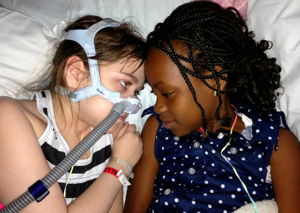 Sarah Murnaghan, left, lies in her hospital bed next to adopted sister Ella on the 100th day of her stay in Children's Hospital of Philadelphia, May 30, 2013. (Murnaghan Family)