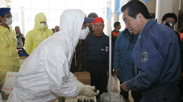 Japanese Prime Minister Naoto Kan, right, speaks to a protective suit-clad employee of Tokyo Electric Power Co. as he visits J-Village, a national training center at Naraha town, Fukushima Prefecture, northeastern Japan, Saturday, April 2, 2011. (AP / Prime Minister's Office of Japan)